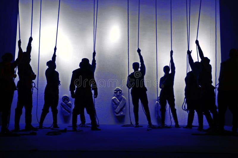 Zwarte silhouetten van mensen met kabels in hun handen bij het theater, Schaduwspel stock foto