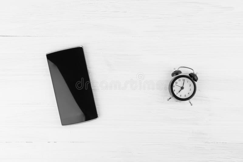 Zwarte Slimme Telefoon naast Wekker met Tweelingklokalarm op Wh stock fotografie