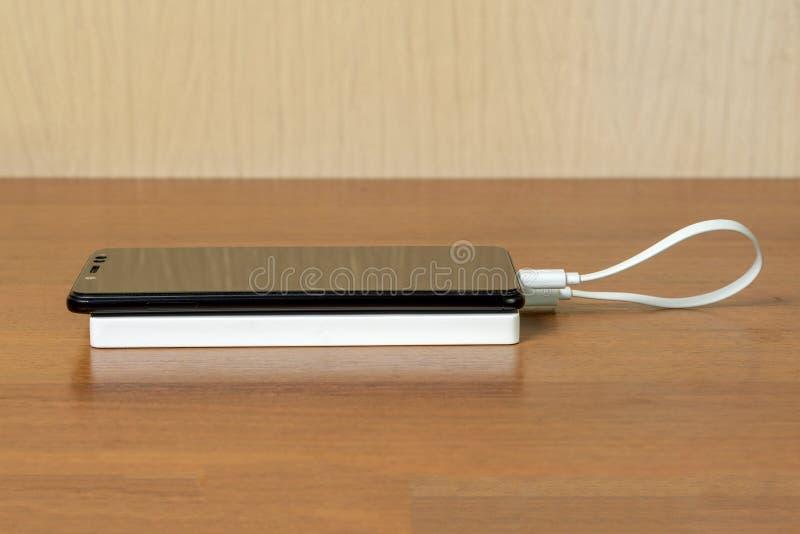 Zwarte smartphone die met witte Machtsbank door USB-Kabel, zijaanzicht belasten stock afbeeldingen