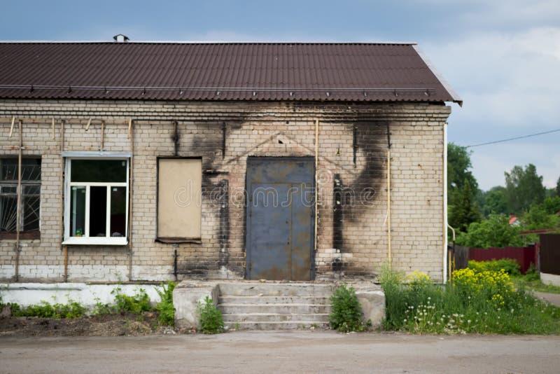 Zwarte sporen van roet op de muur die van het gebouw, na de brand blijft Portiek en nieuwe deur stock foto's