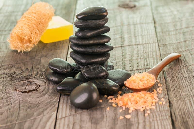 Zwarte stenen, badzout en luffa op doorstaan dek stock afbeelding