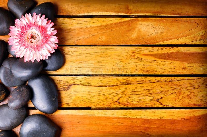 Zwarte stenen en bloem op de linkerkant op houten stock afbeeldingen