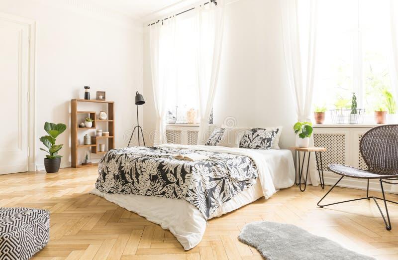 Zwarte stoel dichtbij bed met gevormde bladen in witte slaapkamer inte royalty-vrije stock afbeeldingen