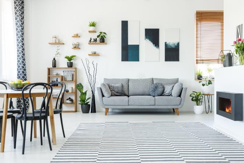 Zwarte stoelen bij lijst in ruim flatbinnenland met affiche royalty-vrije stock afbeelding