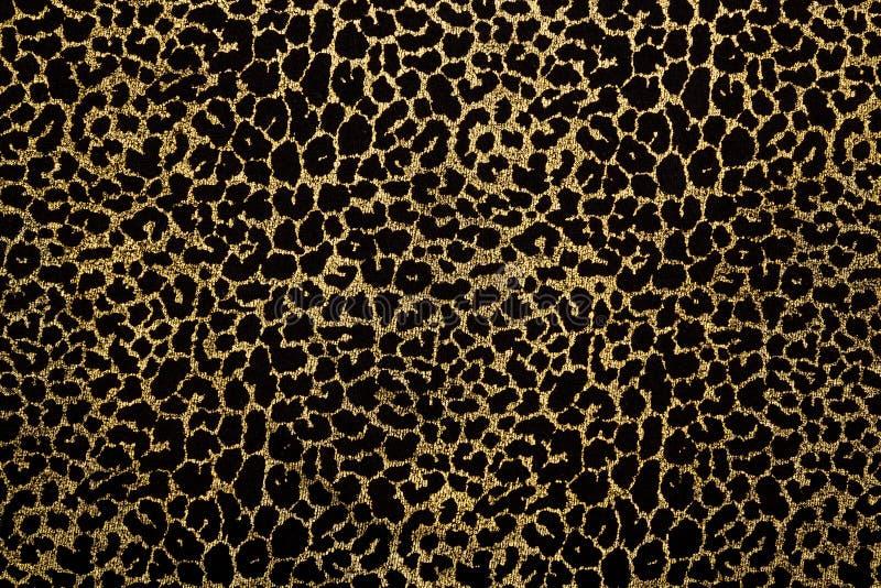 Zwarte stof met de gouden druk van het luipaardbont stock fotografie