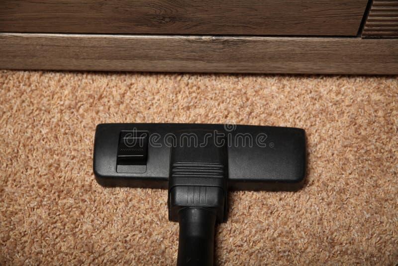 Zwarte stofzuiger op vuil tapijt housework stock afbeeldingen