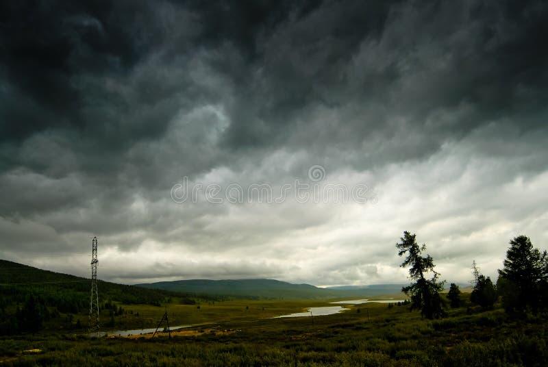 Zwarte stormachtige hemel in de regen in de bergen. stock afbeeldingen
