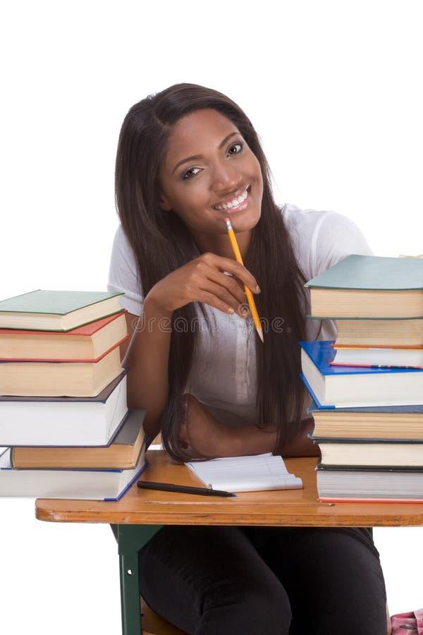 Zwarte studentvrouw door stapel boeken royalty-vrije stock foto's