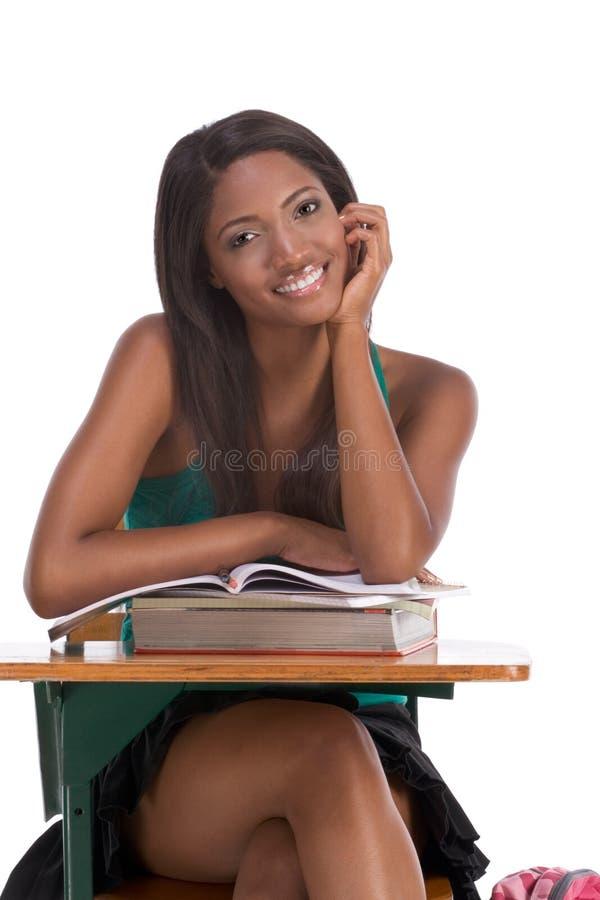 Zwarte studentvrouw met boek door bureau stock foto's