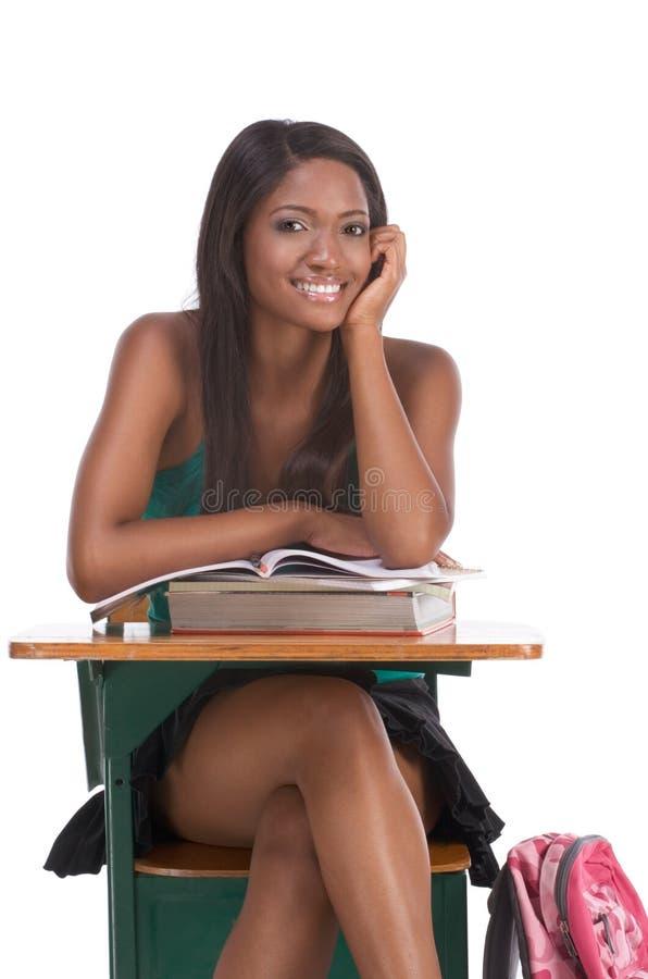 Zwarte studentvrouw met boek door bureau stock afbeeldingen