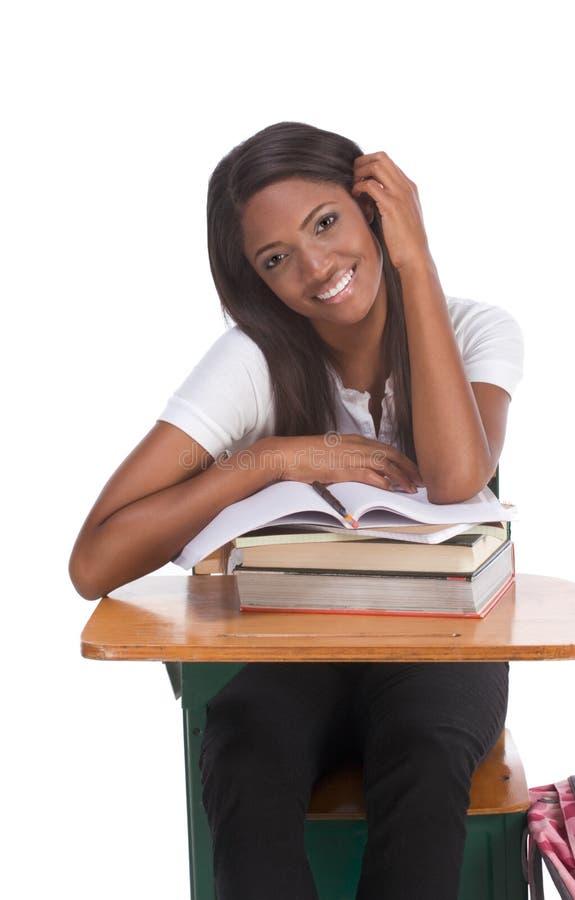 Zwarte studentvrouw met boek door bureau royalty-vrije stock afbeelding