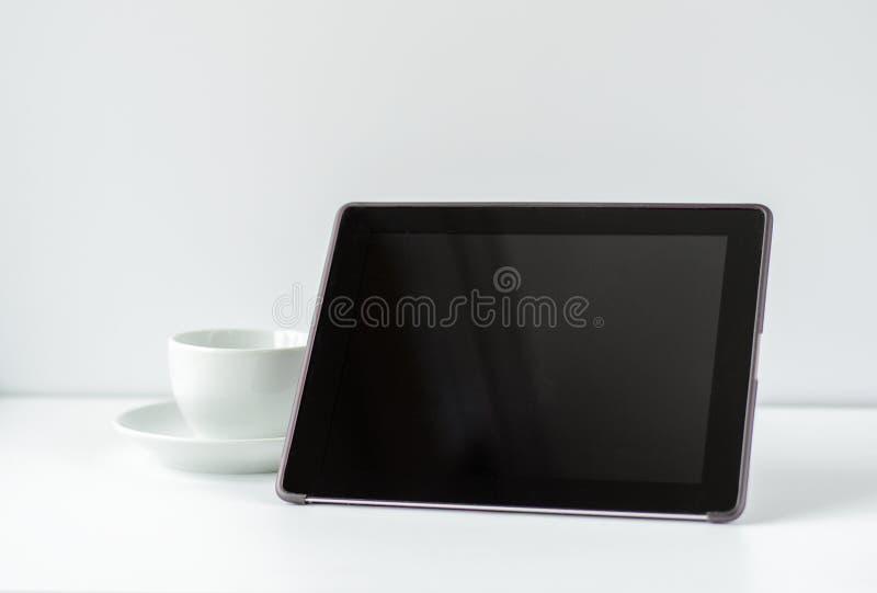 Zwarte tablet met een witte mok op een witte achtergrond Minimale samenstelling, conceptengadget, technologie, mededeling binnen stock afbeelding