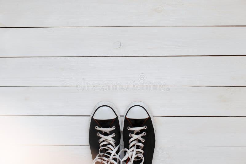 Zwarte tennisschoenen met kant op een witte houten vloer Hoogste mening royalty-vrije stock afbeeldingen