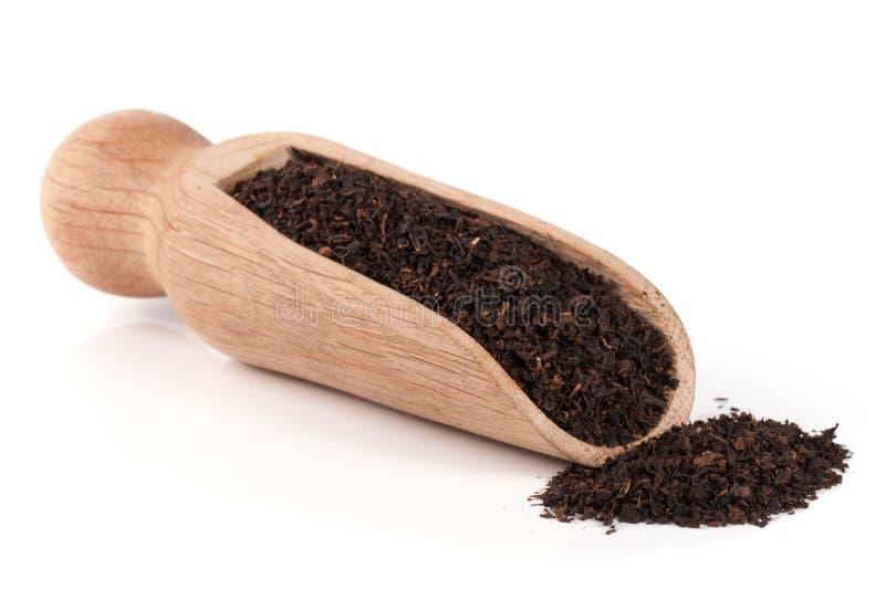 Zwarte thee in een houten die lepel op een witte achtergrond wordt geïsoleerd stock foto
