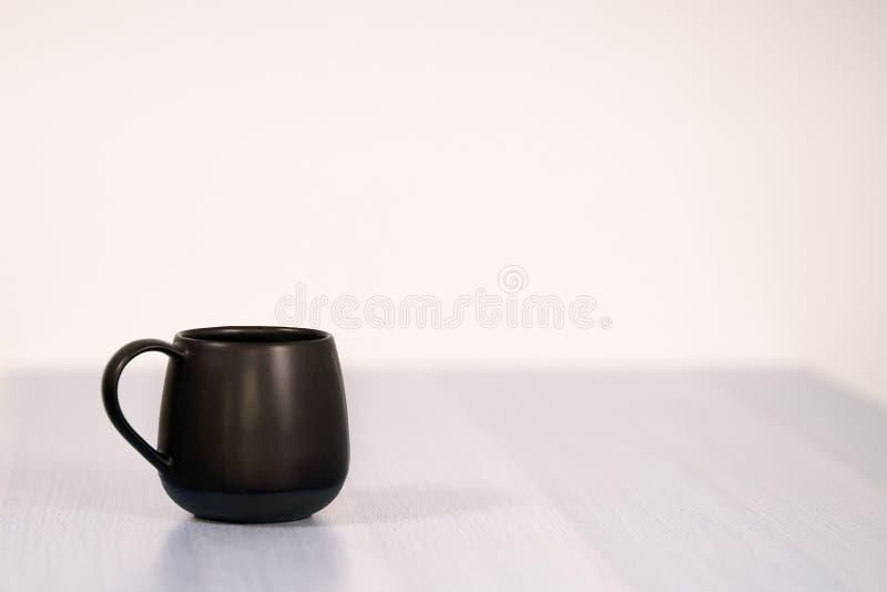Zwarte thee of koffie GLB op de witte houten lijst aangaande witte achtergrond royalty-vrije stock afbeelding