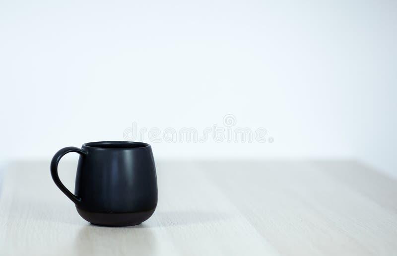 Zwarte thee of koffie GLB op de witte houten lijst aangaande witte achtergrond stock fotografie