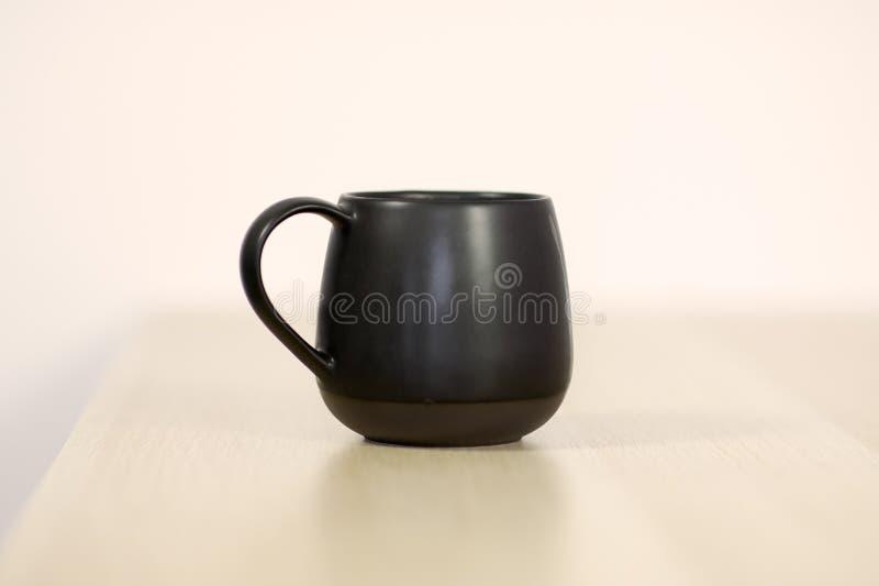 Zwarte thee of koffie GLB op de witte houten lijst aangaande witte achtergrond royalty-vrije stock fotografie