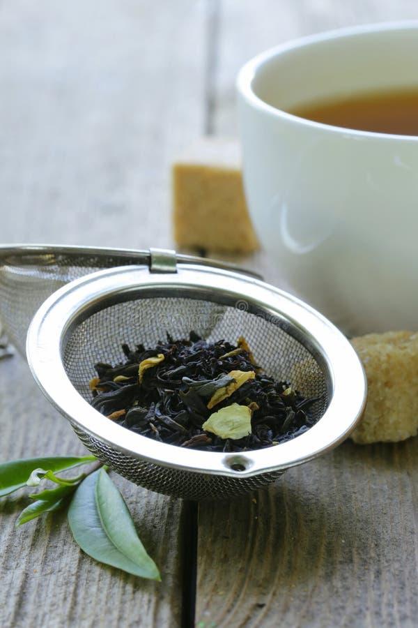 Zwarte theebladen in een metaalzeef stock afbeelding