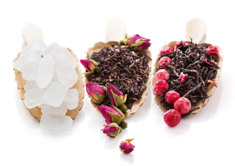 Zwarte theebladen met roze knoppen en bessen en geïsoleerde suiker royalty-vrije stock foto's