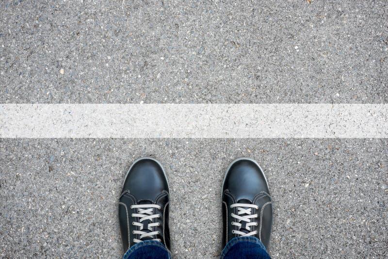 Zwarte toevallige schoenen die zich bij de witte lijn bevinden royalty-vrije stock foto's