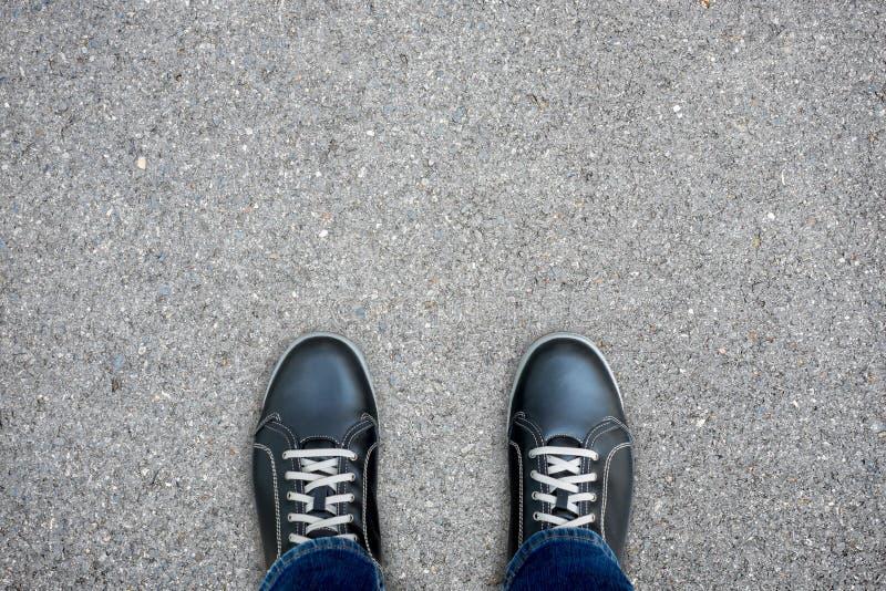Zwarte toevallige schoenen die zich op concrete vloer bevinden stock foto