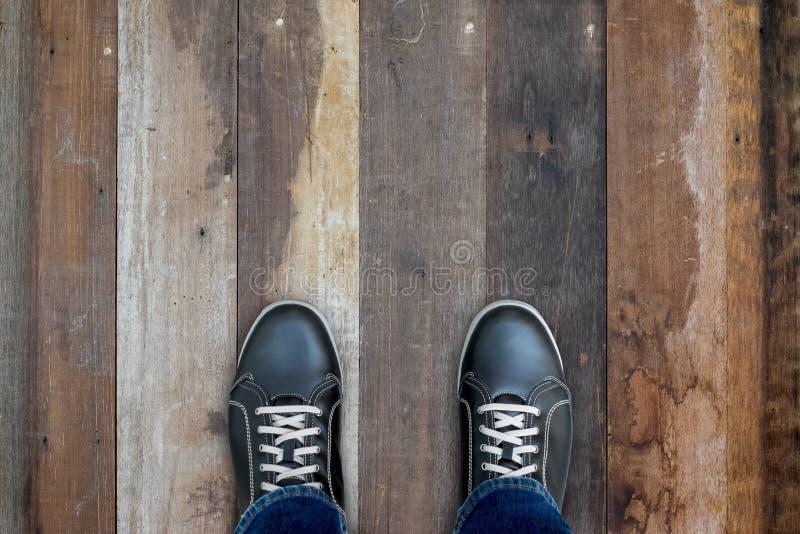 Zwarte toevallige schoenen die zich op houten vloer bevinden royalty-vrije stock afbeeldingen