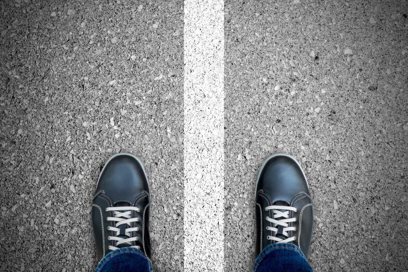 Zwarte toevallige schoenen die zich over witte lijn bevinden royalty-vrije stock fotografie