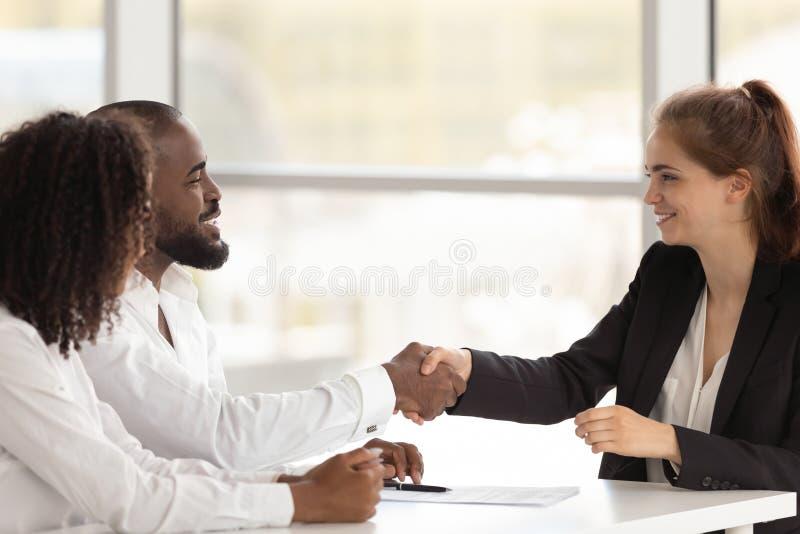 Zwarte u-managerhanddruk met jong vrouwelijk aanvragend beginnend gesprek stock foto