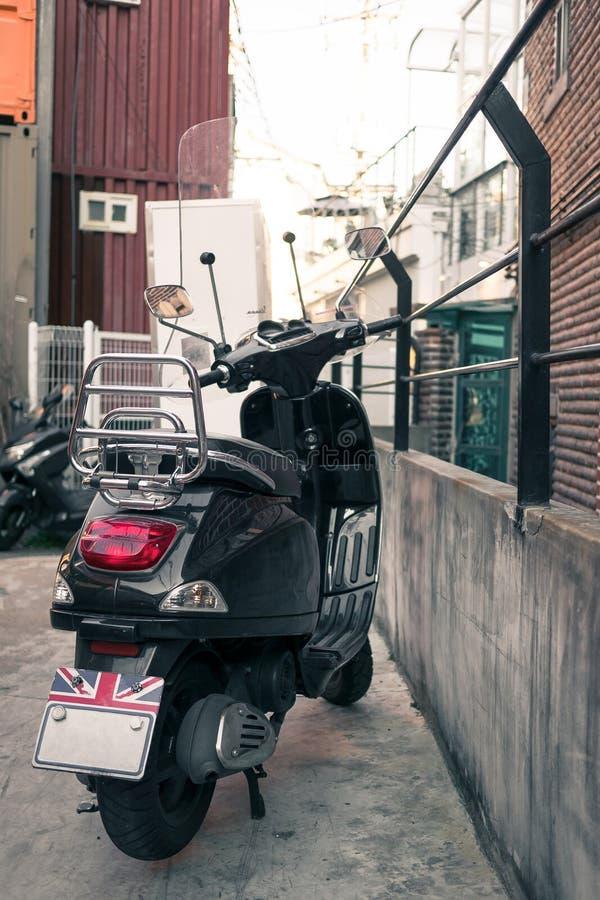 Zwarte uitstekende die autoped in de steeg wordt geparkeerd stock fotografie