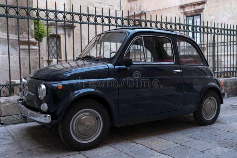 Zwarte uitstekende die cinquecento 500 van Fiat auto voor traliewerk buiten kerk in Puglia, Zuidelijk Italië wordt geparkeerd stock foto