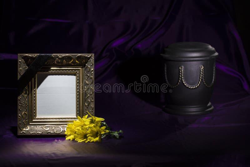 Zwarte urn met gele chrysant en leeg gouden ochtendkader op donkerpaarse achtergrond royalty-vrije stock foto's
