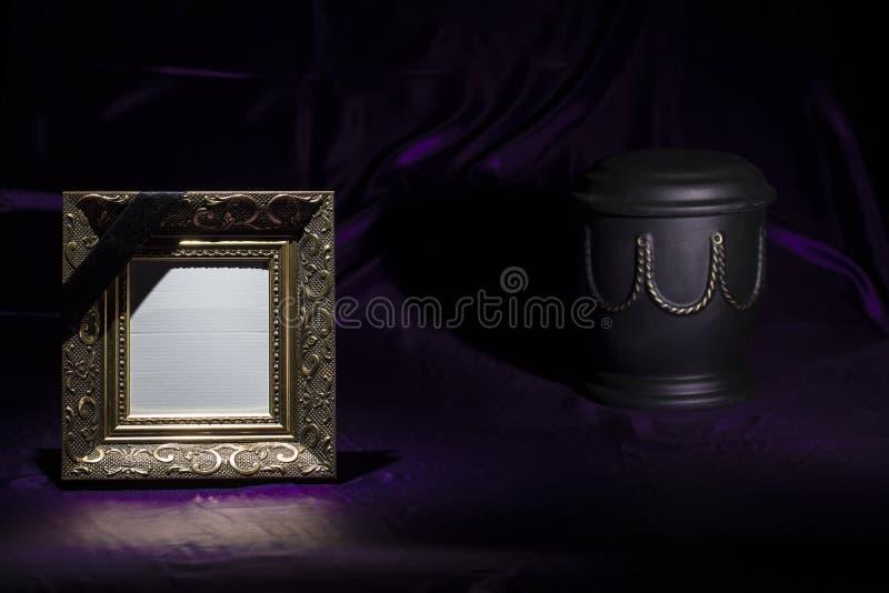 Zwarte urn met gouden decoratie en leeg gouden het rouwen kader royalty-vrije stock foto