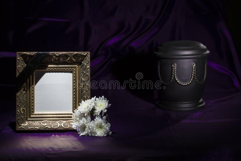 Zwarte urn met gouden decoratie, witte chrysant, lege gouden omlijsting op donkerpaarse achtergrond royalty-vrije stock fotografie