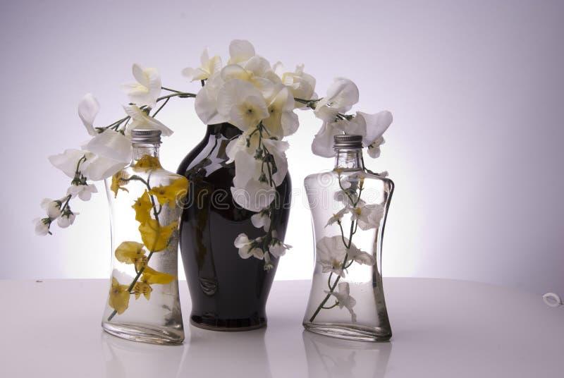 Zwarte vaas met duidelijke flessen en bloemen stock afbeeldingen