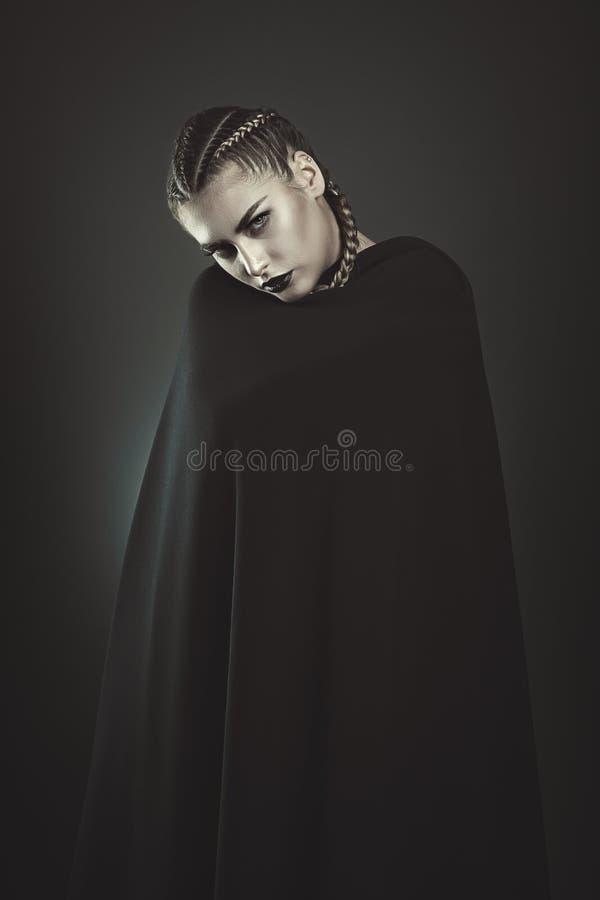 Zwarte vampiervrouw met zwarte mantel stock foto's