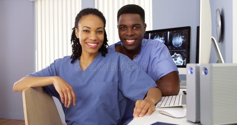 Zwarte verpleegsters in de zitting van de verpleegsterspost bij computer royalty-vrije stock foto