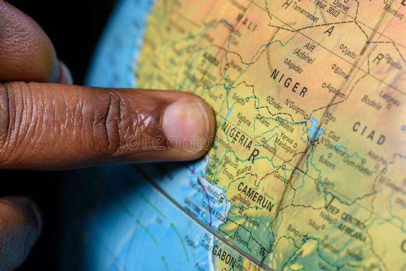 Zwarte vinger die Nigeria op een kaart richten royalty-vrije stock foto's