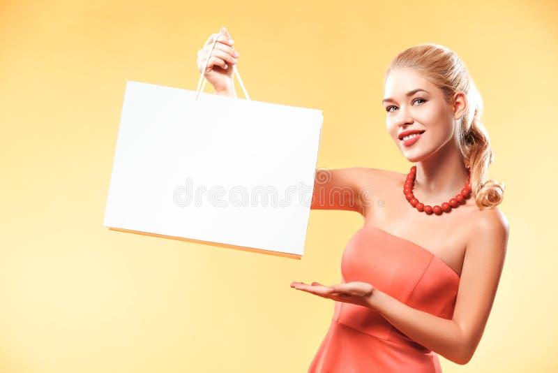 Zwarte vrijdag Gelukkige jonge vrouw die in vakantie winkelen Meisje die op zak met exemplaarruimte tonen royalty-vrije stock foto's