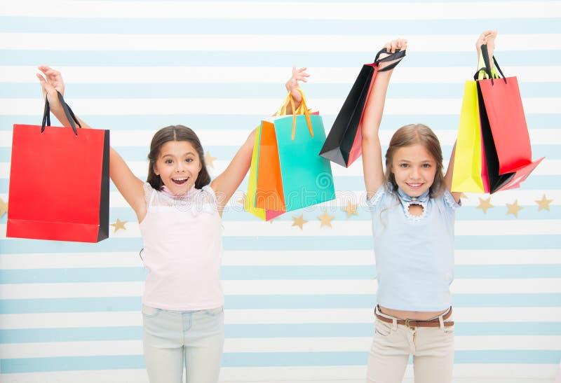Zwarte vrijdag komst De kinderen van jonge geitjesmeisjes met pakketten na het winkelen dag Gelukkige meisjes de vrienden dragen  royalty-vrije stock foto's