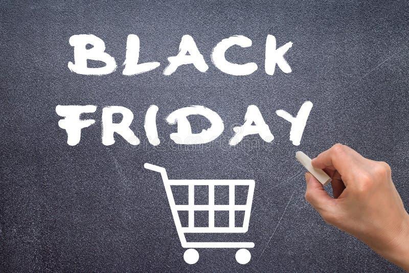 Zwarte vrijdag met de hand geschreven met wit krijt op een bord stock afbeelding
