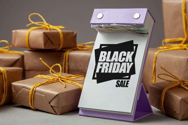 Zwarte vrijdagverkoop Afscheuringskalender en vele giften of pakketten met geel lint in giftdocument op grijze achtergrond stock foto