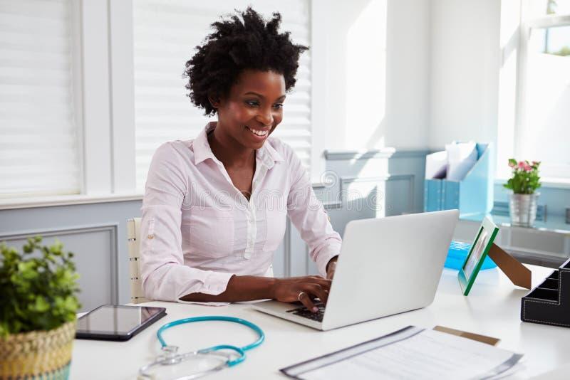 Zwarte vrouwelijke arts aan het werk in bureau die laptop computer met behulp van royalty-vrije stock afbeeldingen