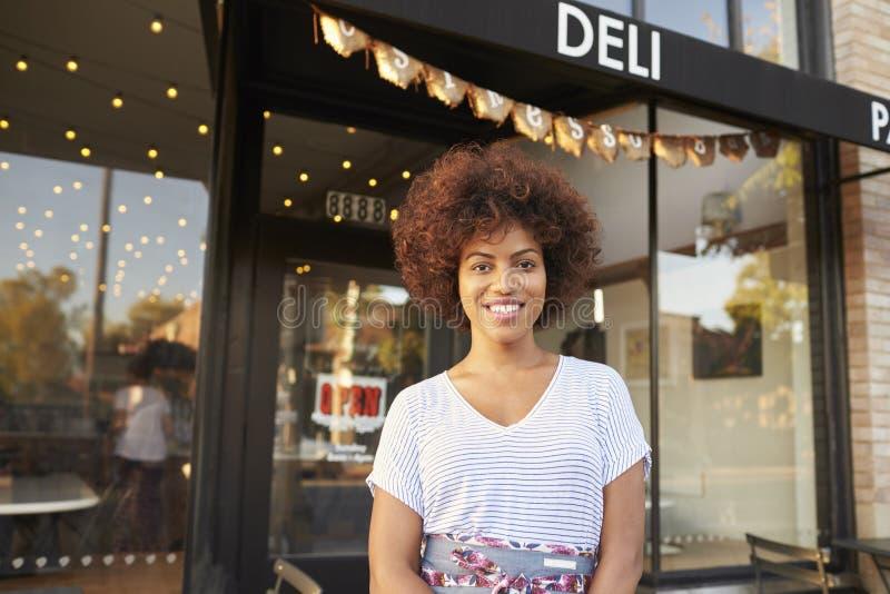 Zwarte vrouwelijke bedrijfseigenaar die zich in straat buiten koffie bevinden stock afbeeldingen