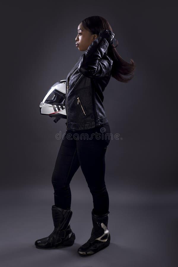 Zwarte Vrouwelijke Raceauto die Haar Haar bevestigen stock foto's