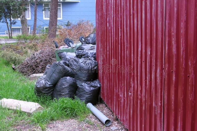 Zwarte vuilniszakken dichtbij de omheining van privé huis en een ten val gebrachte vuilnisbak stock afbeelding