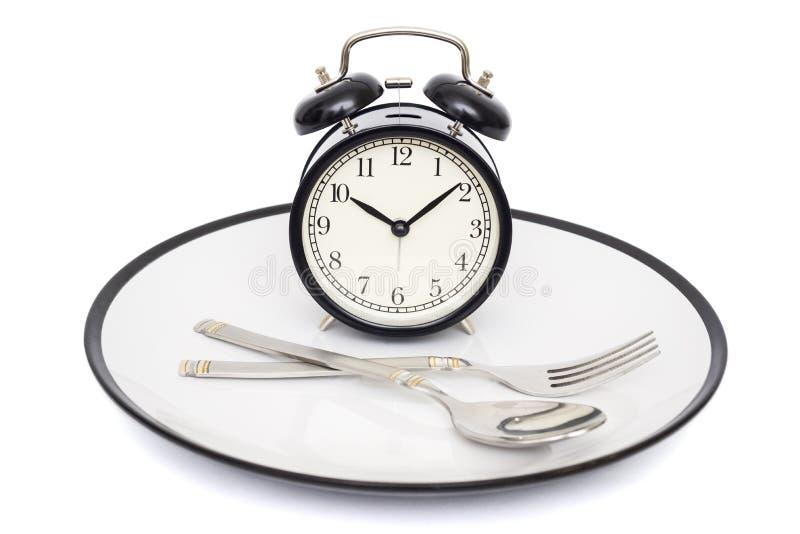 Zwarte wekker met vork en mes op de plaat Geïsoleerd op wit Tijd te eten Gewichtsverlies of dieetconcept royalty-vrije stock afbeeldingen