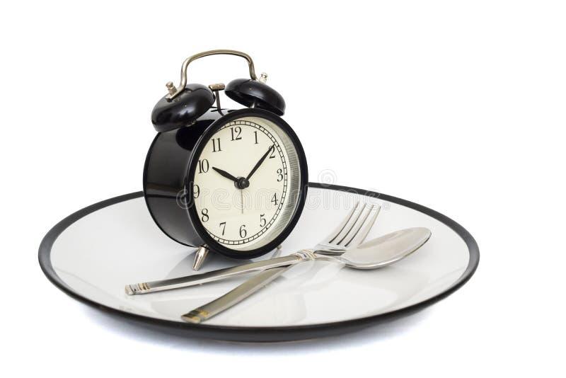 Zwarte wekker met vork en mes op de plaat Geïsoleerd op wit Tijd te eten Gewichtsverlies of dieetconcept royalty-vrije stock foto's