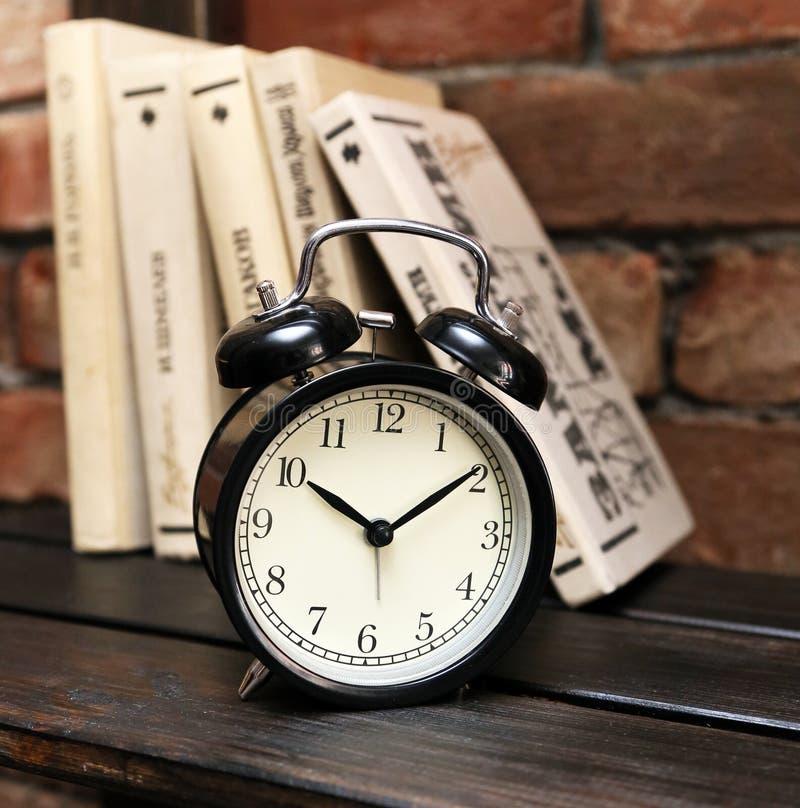 Zwarte wekker op een houten plank op de achtergrond van de boeken en de bakstenen muur stock fotografie