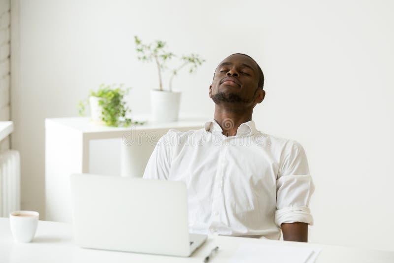 Zwarte werknemer die rust nemen die oefening voor ontspanning doen op het werk royalty-vrije stock foto