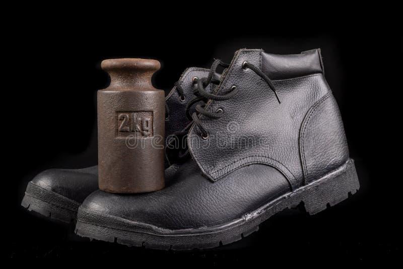 Zwarte werkschoen en 2 kg gewicht Slijpbestendige schoenen voor productiewerkers stock afbeelding